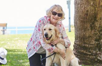 Therese is kneeling and embracing Yael, a Golden Retriever Seeing Eye Dog